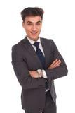Säker ung affärsman som ler med korsade händer Royaltyfri Bild