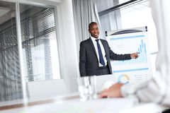 Säker ung affärsman som pekar in mot graf, medan ge presentation i regeringsställning Royaltyfria Foton