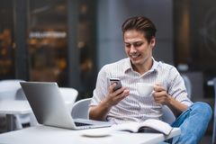 Säker ung man i smarta tillfälliga kläder som rymmer en kopp och talar vid smartphonen arkivbilder