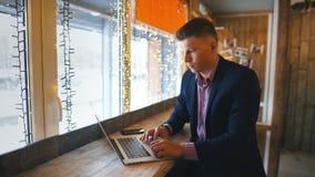 Säker ung man i tillfälliga kläder som arbetar på bärbara datorn, medan sitta nära fönster i idérikt kontor eller kafé arkivfilmer