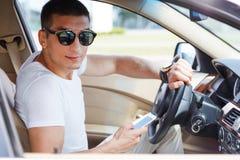 Säker ung rikeman som ställer in hans smarta telefon och ser kameran, medan sitta i bilen royaltyfri bild