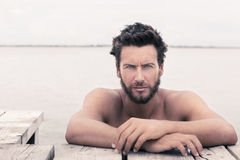 Säker ursnygg stilig man med ingen skjorta på havet royaltyfri fotografi