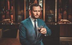 Säker välklädd man med exponeringsglas av whisky i lyxig lägenhetinre royaltyfria bilder