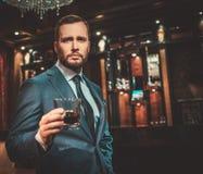 Säker välklädd man med exponeringsglas av whisky i lyxig lägenhetinre royaltyfri fotografi