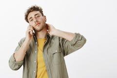 Säker varm lockig-haired manlig modell med skägget, lyftande huvudet och den rörande halsen, medan tala på smartphonen som står arkivbilder