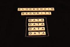 Säkerhet för kvarterkedja som stavas ut i tegelplattor på en svart bakgrund med en grupp av data som under omges av kedjor Arkivfoton