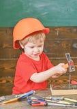 Säkerhet på arbetsplatsen Den lilla ungen i orange bulta för hjälm spikar Gullig pojke som spelar med hjälpmedel royaltyfria foton