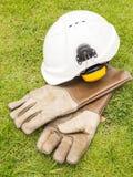 Säkerhetsörat muffs hjälmen och lågtemperatur- läderhandskar för industr Arkivfoton