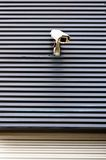 Säkerhetscctv-kamera på en vägg av kommersiellt byggande Arkivfoto
