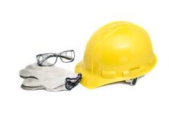 Säkerhetshjälm, exponeringsglas och handskar på vit med den snabba banan Arkivbilder