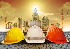 Säkerhetshjälm och byggnadskonstruktion som skissar på skrivbordsarbetebruk för affär för konstruktionsbransch och arkitekturengin Royaltyfri Foto