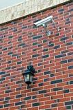 Säkerhetskamera och ficklampa på väggen arkivbild