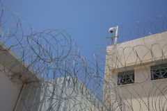 Säkerhetskamera ovanför taggtråd i fängelse royaltyfri fotografi