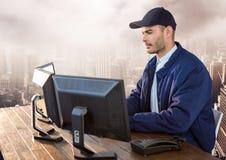 Säkerhetsman på datoren över stor stad royaltyfri foto