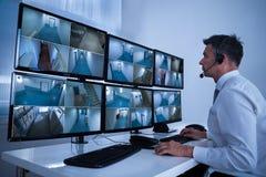 Säkerhetssystemoperatör som ser CCTV-längd i fot räknat på skrivbordet Royaltyfri Fotografi