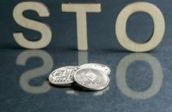 Säkerhetstecken som erbjuder STO-tecknet med träbokstäver och silvermynt som är främsta av det, Ethereum begrepp arkivbild