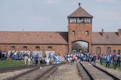 Säkerhetstornet på ingången till den Auschwitz Birkenau koncentrationsläger med gruppen av ungar på mars av uppehället arkivfoto