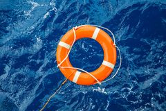 Säkerhetsutrustning, livboj eller räddningsaktionboj som svävar på havet för att rädda folk från drunkningman Arkivbilder