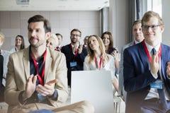 Säkert affärsfolk som applåderar under seminarium Royaltyfria Bilder
