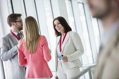 Säkert affärsfolk som diskuterar i ljust tänd konventcentrum Arkivfoto