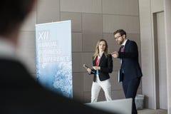 Säkert affärsfolk som diskuterar, medan gå i konventcentrum Royaltyfri Foto