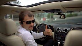 Säkert affärsmansammanträde i bilen som ger tummar-upp, gör en gest, affärschauffören arkivbilder