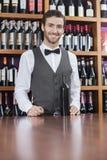 Säkert bartenderWith Wine Bottle anseende på räknaren arkivbilder