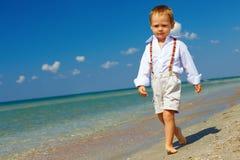 Säkert behandla som ett barn pojken går framåtriktat den fasta gåenden Arkivfoton