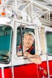 Säkert brandmansammanträde i Firetruck Fotografering för Bildbyråer
