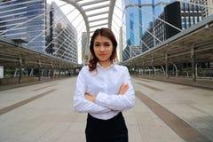 Säkert kvinnabegrepp för ledare Stående av den unga eleganta asiatiska affärskvinnan som står och ser till kameran på den stads-  Fotografering för Bildbyråer
