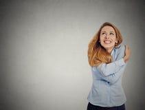 Säkert kvinnainnehav som kramar sig som ser upp Arkivbilder