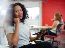 Säkert kvinnligt märkes- arbete på en digital minnestavla i rött idérikt kontorsutrymme Arkivfoto