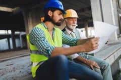 Säkert lag av arkitekter och teknikerer som tillsammans arbetar på konstruktionsplats fotografering för bildbyråer