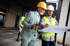 Säkert lag av arkitekter och teknikerer som tillsammans arbetar på konstruktionsplats arkivfoton