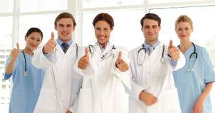 Säkert medicinskt lag som ser kameran och ger upp tummar lager videofilmer
