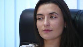 Säkert moget affärskvinnasammanträde i en fåtölj i regeringsställning Kvinnlig chef i regeringsställning som ser kameran långsamt stock video