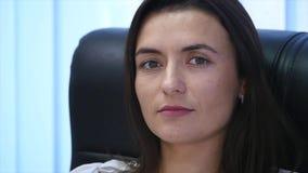 Säkert moget affärskvinnasammanträde i en fåtölj i regeringsställning Kvinnlig chef i regeringsställning som ser kameran långsamt arkivfilmer