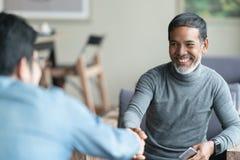 Säkert moget asiatiskt mansammanträde som ler och skakar handen med partnerskap, når framställning av lönande överenskommelse arkivfoton