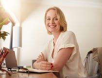 Säkert moget kvinnasammanträde på det funktionsdugliga skrivbordet royaltyfri foto