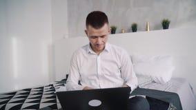 Säkert och le mannen som hemma använder bärbara datorn arkivfilmer