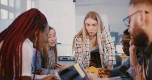 Säkert positivt kvinnligt företagsframstickande som arbetar samman med yrkesmässiga multietniska partners på brädelagmötet arkivfilmer