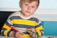 säkert skrivbord för pojke little som sitter arkivbilder