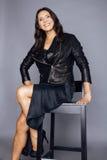 Säkert stilfullt verkligt moget kvinnasammanträde för nätt brunett på stol i studion som är sexig på bärande läder för grå bakgru fotografering för bildbyråer