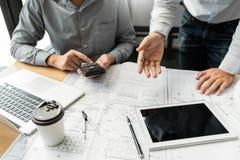 Säkert teknikerlag som arbetar med det blåa trycket med arkitektutrustning som diskuterar och planerar projekt för konstruktion f arkivbild