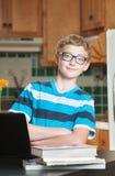 Säkert tonårigt med läroböcker i kök Arkivbild