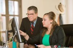 Säkert yrkesmässig kvinna- och manarbete på datoren arkivfoton