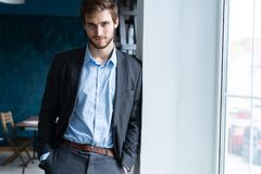 Säkert yrkesmässigt stiligt affärsmananseende nära fönster i hans kontor arkivbilder