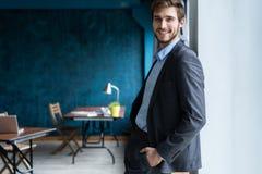 Säkert yrkesmässigt stiligt affärsmananseende nära fönster i hans kontor arkivfoto