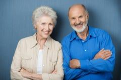 Säkra åldringpar med vikta armar royaltyfria bilder