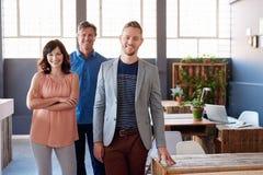 Säkra affärskollegor som tillsammans står i ett modernt kontor arkivfoto